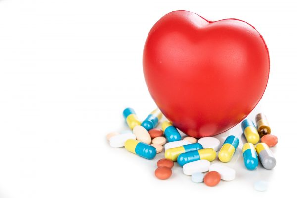 Healthcare concept with medicine pills, caplet, tablet, capsule and red heart as prop